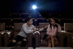 Interracial couple on a movie theater date. Young interracial dating couple in a movie theater watching a show.  The men is asian and the women is black.  They Royalty Free Stock Image