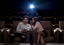 Interracial couple on a movie theater date. Young interracial dating couple  in a movie theater