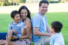Young interracial family fun outdoor. Portrait joyful young interracial hispanic caucasian family, relaxed together in park outdoors, blurred background Stock Image