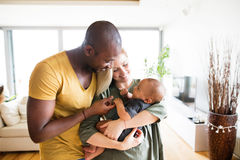 Young interracial family with little baby son at home. Royalty Free Stock Image