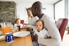 Young interracial family with little children having breakfast. Royalty Free Stock Image