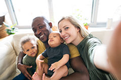 Young interracial family with little children taking selfie. Stock Images