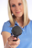 Young interviewer holding a microphone Stock Photos