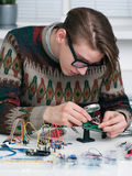 Young inventor examing electronic component Royalty Free Stock Image