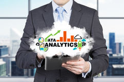 Young investment banker is holding a cloud with analytic solutions for business. Stock Photos