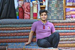 A young Iranian trader in fabric store, Shiraz, Iran. Fars Province, Shiraz, Iran - 19 april, 2017: One young Iranian male salesman is sitting in front of his royalty free stock photo
