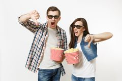 Young irritated couple, woman and man in 3d glasses and casual clothes watching movie film on date, holding buckets of