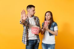 Young irritated couple woman man watching movie film on date holding bucket of popcorn and plastic cup of soda or cola stock photos