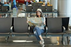 Young irritated traveler tourist woman holding paper map, search route, screaming waiting in lobby hall at airport. Passenger traveling abroad on weekends stock image