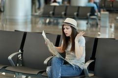 Young irritated traveler tourist woman holding paper map, search route, spread hands, wait in lobby hall at airport royalty free stock photography