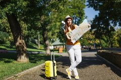 Young irritated traveler tourist woman in yellow summer casual clothes, hat with suitcase city map walk in city outdoor stock images