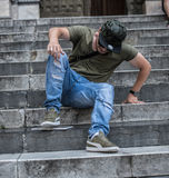 Angry guy stomping on his tablet. A young Italian guy angry at his old tablet, trying to stomp on it and destroying it his feet Royalty Free Stock Photo