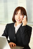 Young Japanese business woman talks with a smart phone Royalty Free Stock Photos
