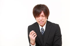 Young Japanese businessman cries. Studio shot of young Japanese businessman on white background Royalty Free Stock Image