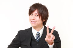 Young Japanese Businessman showing a victory sign Royalty Free Stock Images