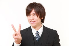 Young Japanese businessman showing a victory sign Stock Images