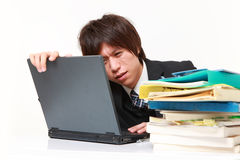 Young Japanese businessman shrinks from overtime work royalty free stock images
