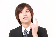 Young Japanese businessman thinks about something . Studio shot of young Japanese man on white background royalty free stock photography