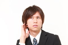 Young Japanese businessman worries about something. Studio shot of young Japanese man on white background stock photo