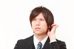 Young Japanese businessman worries about something. Studio shot of young Japanese businessman on white background Royalty Free Stock Photo