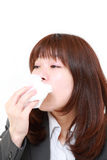 young Japanese businesswoman with an allergy sneezing into tissue Stock Photo