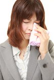 Young Japanese businesswoman cries. Studio shot of young Japanese businesswoman on white background Stock Image