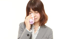 Young Japanese businesswoman cries. Studio shot of young Japanese businesswoman on white background Royalty Free Stock Photography