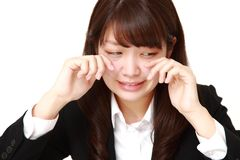 Young Japanese businesswoman cries. Studio shot of young Japanese woman on white background Stock Images