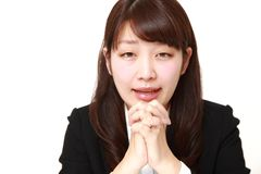 Young Japanese businesswoman folding her hands in prayer Royalty Free Stock Images