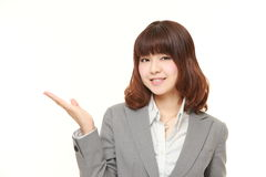 Young Japanese businesswoman presenting and showing something. Studio shot of young Japanese businesswoman on white background stock photos