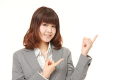 Young Japanese businesswoman presenting and showing something. Studio shot of young Japanese businesswoman on white background royalty free stock photos