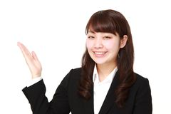 Young Japanese businesswoman presenting and showing something. Studio shot of young Japanese woman on white background Stock Images