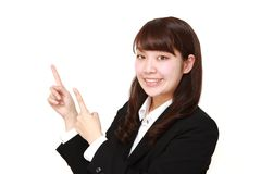 Young Japanese businesswoman presenting and showing something. Studio shot of young Japanese woman on white background Royalty Free Stock Photography
