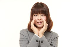 Young Japanese businesswoman shout something. Studio shot of young Japanese businesswoman on white background stock photography