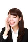 Young Japanese businesswoman shout something. Studio shot of young Japanese woman on white background stock photography