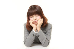 Young Japanese businesswoman sleeping on the desk Stock Photos