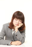 Young Japanese businesswoman sleeping on the desk Royalty Free Stock Photos