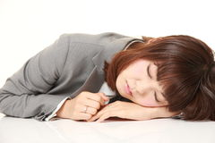 Young Japanese businesswoman sleeping on the desk Stock Photography
