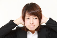 Young Japanese businesswoman suffers from noise Stock Image