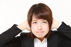 Young Japanese businesswoman suffers from noise Stock Photography