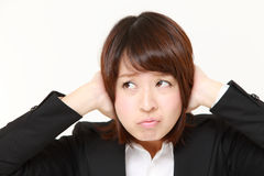 Young Japanese businesswoman suffers from noise Royalty Free Stock Photography