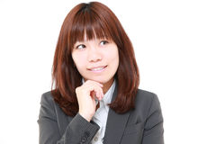 Young Japanese businesswoman thinks about something. Studio shot of young Japanese businesswoman on white background Stock Image