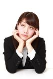 Young Japanese businesswoman thinks about something. Studio shot of young Japanese woman on white background stock images
