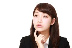 Young Japanese businesswoman thinks about something. Studio shot of young Japanese woman on white background royalty free stock photo