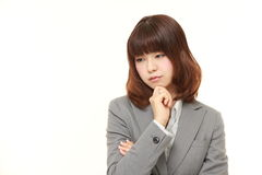 Young Japanese businesswoman worries about something. Studio shot of young Japanese businesswoman on white background Royalty Free Stock Photo