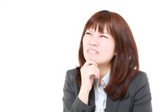 Young Japanese businesswoman worries about something. Studio shot of young Japanese businesswoman on white background stock images