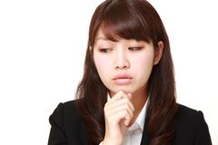 Young Japanese businesswoman worries about something. Studio shot of young Japanese woman on white background Stock Image