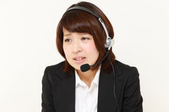Young Japanese businesswomanof call center perplexed to a complaint telephone Stock Image