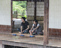 A young Japanese couple look at the rain from the temple buildi Stock Images