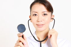 Young Japanese female doctor auscultating with stethoscope Stock Photos